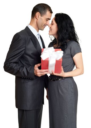 studio background: Couple with gift box, studio portrait on white. Dressed in black suit.