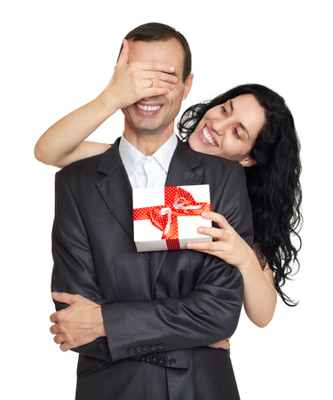 spaniard: Couple with gift box, studio portrait on white. Woman close man eyes. Dressed in black suit. Stock Photo