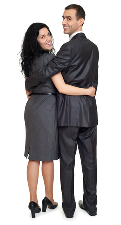 relationship love: Couple embrace backside, rear view, studio portrait on white. Dressed in black suit.