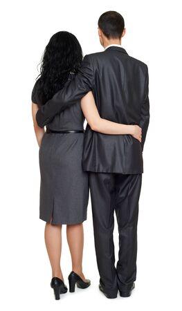 studio portrait: Couple embrace backside, rear view, studio portrait on white. Dressed in black suit.