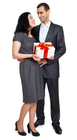 marido y mujer: Pares con la caja de regalo, retrato de estudio en blanco. Vestido de traje negro. Foto de archivo