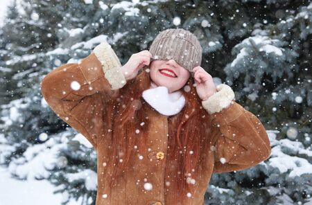 blinded: Winter woman blinded snow on head, fir trees background