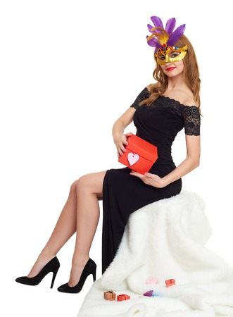 evening gown: Woman in black evening gown and carnival mask with gift box. Sit on white fur. Valentine holiday and party concept.
