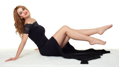 naked girl black hair: girl with bare legs lying on white fur, wearing a black dress. Stock Photo