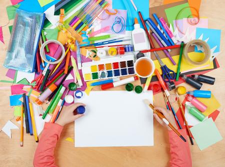 Illustrazione del bambino vista dall'alto. posto di lavoro Opera con gli accessori creativi. Piatti strumenti di arte laici per la pittura.