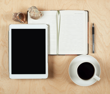 blank center: Flat lay of tablet computer, notebook, coffee cup  and pencil with blank center on wood background, top view Stock Photo