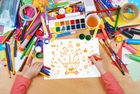 stuff toys: child drawing baby stuff - pram, wear and toys, top view hands with pencil painting picture on paper, artwork workplace