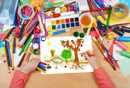 kitchen garden: child drawing kitchen garden with vegetables , top view hands with pencil painting picture on paper, artwork workplace