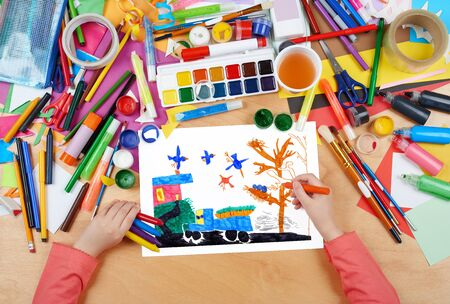 birds eye view: car with vegetables crop and birds, child drawing , top view hands with pencil painting picture on paper, artwork workplace