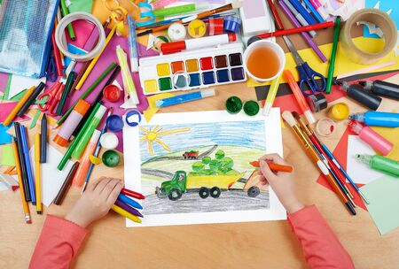 truck driver: harvesting, truck with vegetables goes off field, dog driver, agriculture concept, child drawing, top view hands with pencil painting picture on paper, artwork workplace