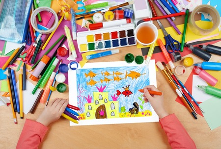 under view: castle under water with treasure, the king fish with crown, fairy tale, child drawing, top view hands with pencil painting picture on paper, artwork workplace