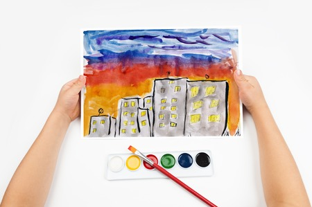 skyscraper sky: city skyline at sunset, skyscraper with light in window, home silhouette on dark sky background, child drawing, top view hands with pencil painting picture on paper, artwork workplace