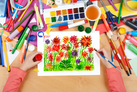 flower bed: flower bed meadow closeup background, child drawing, top view hands with pencil painting picture on paper, artwork workplace
