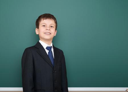 successfull: happy successfull school boy in black suit portrait on green chalkboard background, education concept