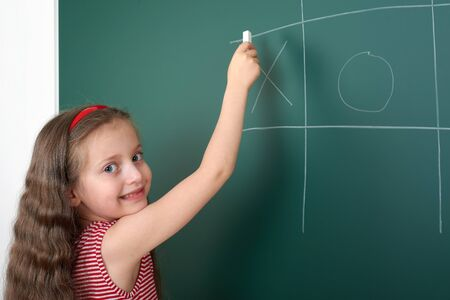 tic tac toe: schoolgirl child in red striped dress drawing tic tac toe on green chalkboard background, summer school vacation concept
