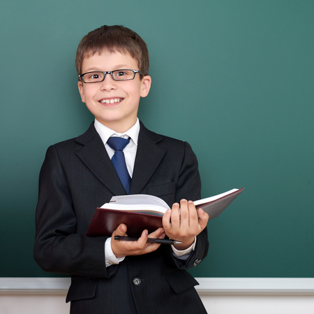 successfull: happy successfull school boy with book portrait, dressed in classic black suit, on green chalkboard background, education and business concept Stock Photo