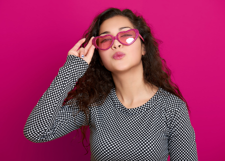 flying kiss: young woman beautiful portrait make flying kiss, posing on pink background, long curly hair, sunglasses in heart shape, glamour concept