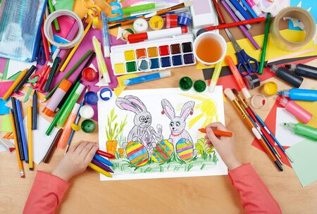 holiday picture: rabbit family on meadow with eggs, easter holiday concept, child drawing, top view hands with pencil painting picture on paper, artwork workplace