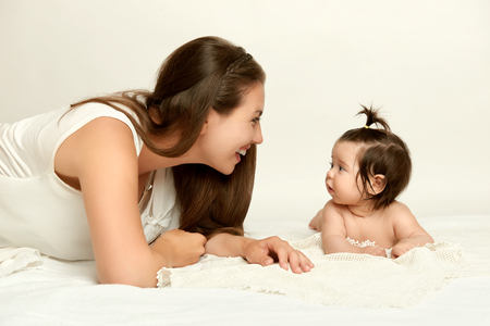 portrait of mother and baby having fun, lie on white, yellow toned Фото со стока