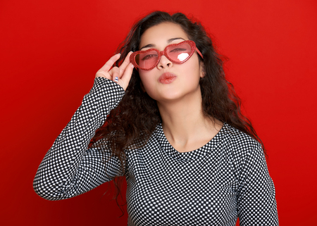 flying kiss: young woman beautiful portrait flying kiss, posing on red background, long curly hair, sunglasses in heart shape, glamour concept