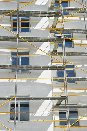 house under construction: scaffolding near a house under construction for external plaster works, high apartment building in city, white wall and window, yellow pipe