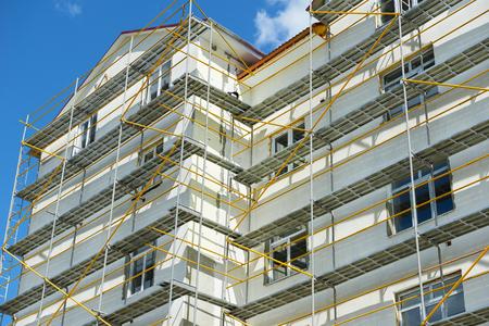 scaffolder: scaffolding near a house under construction for external plaster works, high apartment building in city, white wall and window, yellow pipe