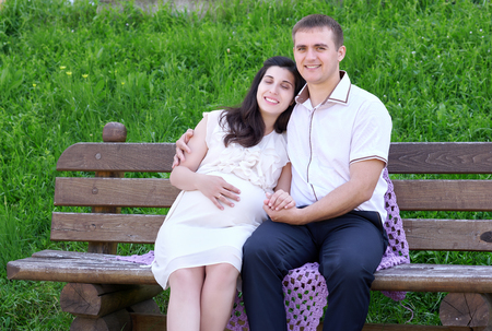 ojos cerrados: pregnant woman closed eyes and dreaming, and husband on outdoor, happy family, couple in city park, summer season, green grass and trees