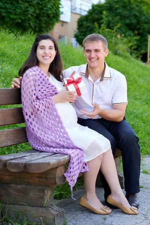 bow belly: pregnant woman takes a gift from her husband, happy family, couple in city park, summer season, green grass and trees