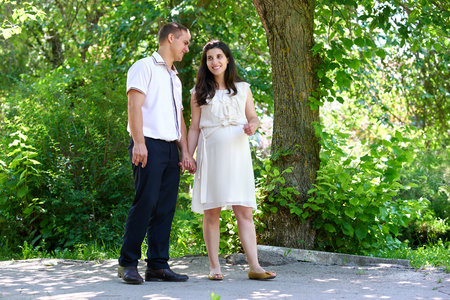 sidewalk talk: pregnant woman with husband walking in the city park, family portrait, summer season, green grass and trees