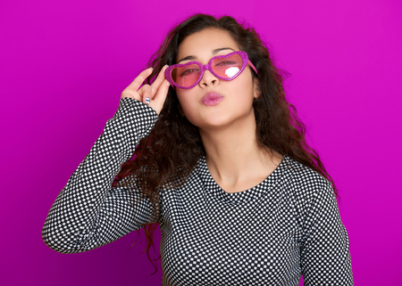 flying kiss: young woman beautiful portrait flying kiss, posing on purple background, long curly hair, sunglasses in heart shape, glamour concept