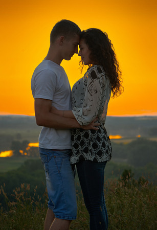 nightfall: romantic couple at sunset on bright yellow sky background, love tenderness concept, young adult people Stock Photo