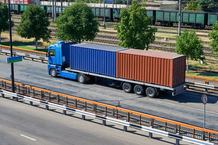 consignment: truck with containers in seaport, cargo shipping and transportation concept
