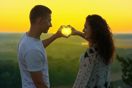 joven pareja al atardecer hacer una forma de corazón de las manos, los rayos del sol brillan a través de las manos, hermoso paisaje y el cielo de color amarillo brillante, concepto de amor la ternura