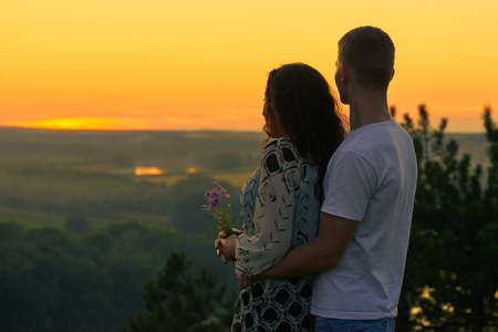 romantic couple look on sunset on country outdoor, beautiful landscape and bright yellow sky, love tenderness concept, young adult people Stock Photo