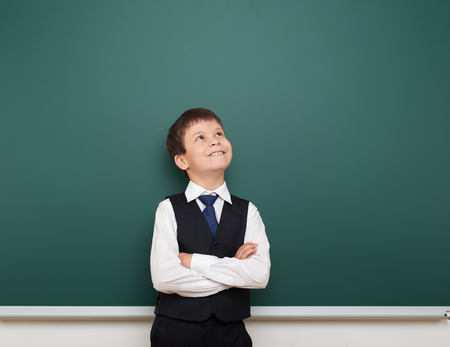 schoolkid: school student boy look up at the clean blackboard, grimacing and emotions, dressed in a black suit, education concept, studio photo Stock Photo