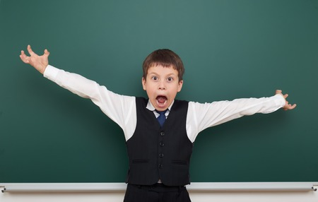 schoolkid: school student boy posing at the clean blackboard and open arms, grimacing and emotions, dressed in a black suit, education concept, studio photo