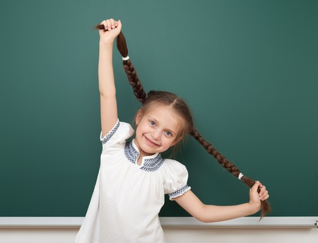 schoolkid: school student girl open arms at the clean blackboard, grimacing and emotions, dressed in a black suit, education concept, studio photo