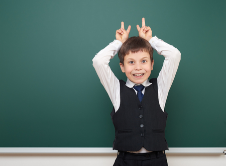 schoolkid: school student boy posing at the clean blackboard, grimacing and emotions, dressed in a black suit, education concept, studio photo Stock Photo