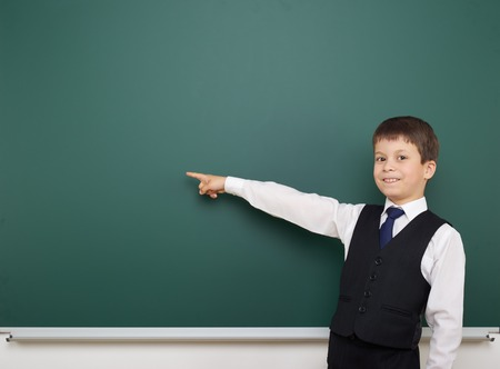 schoolkid: school student boy posing at the clean blackboard, show finger and point at, grimacing and emotions, dressed in a black suit, education concept, studio photo Stock Photo