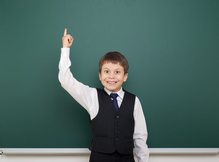 schoolkid: school student boy posing at the clean blackboard, show finger up and point, grimacing and emotions, dressed in a black suit, education concept, studio photo