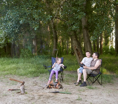 hatchet man: people camping in forest, family active in nature, kindle fire, summer season