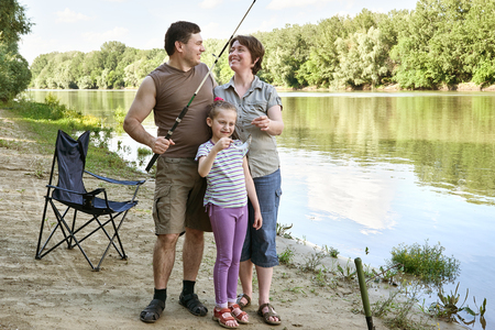 people camping and fishing, family active in nature, fish caught on bait, river and forest, summer season Stock Photo