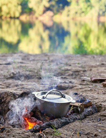 cooking on fire at picnic, food prepared in kettle on wood, trees reflected in river, healthy vegetarian food