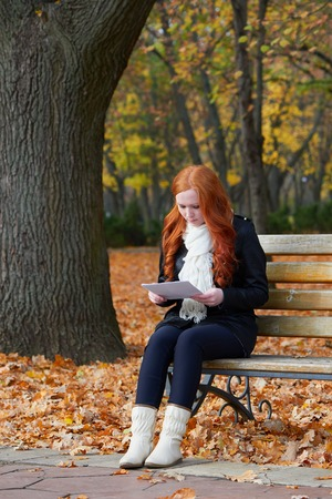 one sheet: redhead girl in autumn city park read paper sheet, sit on wood bench, one people at day, yellow leaves fall