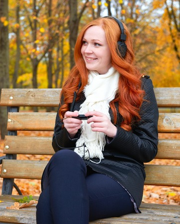 player bench: girl in fall season listen music on audio player with headphones, sit on bench in city park, yellow trees and fallen leaves