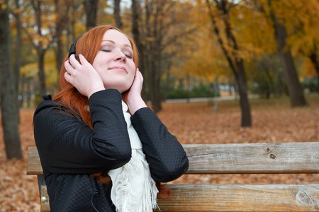 player bench: girl portrait, listen music on audio player with headphones, sit on bench in city park, autumn season, yellow trees and fallen leaves Stock Photo