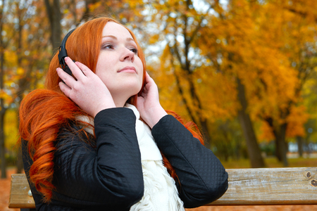 player bench: girl listen music on audio player with headphones, sit on bench in city park, autumn season, yellow trees and fallen leaves
