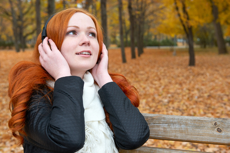 fallen tree: girl listen music on audio player with headphones, sit on bench in city park, autumn season, yellow trees and fallen leaves