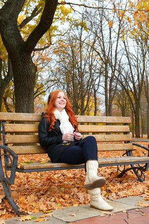 player bench: girl in autumn season listen music on audio player with headphones, sit on bench in city park, yellow trees and fallen leaves