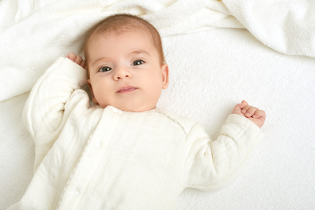 awake: baby portrait lie on white towel in bed, yellow toned